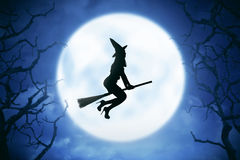 Silhouette of witch woman riding magic broom. Silhouette of witch woman flying on the sky, with moonlight backround. Halloween concept image stock photo