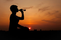 Silhouette woman. Drinking water at sunset Royalty Free Stock Image