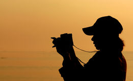 Silhouette Woman. Woman is shooting Photo.Sky is Orange at Sunset.Backlight make Silhouette Stock Photography