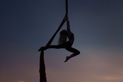 Silhouette of a woman acrobat. Royalty Free Stock Photos