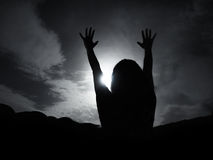 Silhouette of woman against full moon with hands up Royalty Free Stock Photo