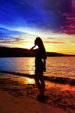 Silhouette of the woman against a sunset at ocean Stock Images