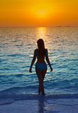 Silhouette of the woman against a sunset ocean Royalty Free Stock Images