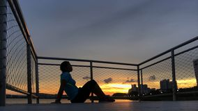 Silhouette of woman against sunset on a pier. Silhouette of a lone woman against the evening sunset on a pier Stock Photo