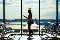 Silhouette of woman in an airport lounge waiting. Silhouette of passenger in an airport lounge waiting for flight aircraft Royalty Free Stock Image