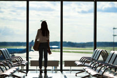 Silhouette of woman in an airport lounge waiting. Silhouette of passenger in an airport lounge waiting for flight aircraft Stock Photography