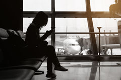 Silhouette of woman at the airport with mobile phone and backpac Stock Photo