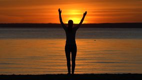 Silhouette of woman with arms raised standing on ocean sea beach looking on waves at sunset. Girl practicing fitness stock footage