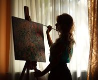 Silhouette woman artist drawing paint picture on easel indoors. Silhouette woman artist drawing paint picture on easel, backlight portrait indoors royalty free stock image