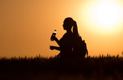 Silhouette of woman with backpack and bottle of water Royalty Free Stock Images