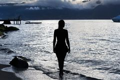 Silhouette of a woman on the beach at sunset. royalty free stock photos