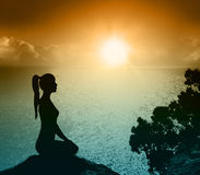 Silhouette of a woman on the beach. Yoga and meditation. Royalty Free Stock Images
