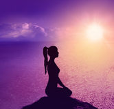 Silhouette of a woman on the beach. Yoga and meditation. Silhouette of a woman on the beach at sunrise.Yoga and meditation royalty free stock image