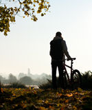 Silhouette of woman with bicycle Stock Photos