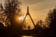 Silhouette of woman on bicycle on suspended bridge under the river by sunset