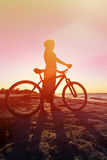 Silhouette of woman biking at sunset Royalty Free Stock Photography
