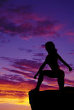 Silhouette of a woman in a bikini on a cliff kneel in sunset Royalty Free Stock Images