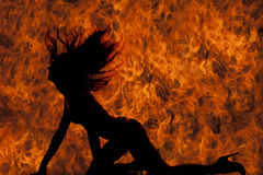 Silhouette woman in bikini hands and knees flip hair fire Stock Photo
