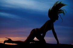 Silhouette woman in bikini on hands and knees hair flipping Stock Images