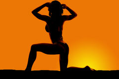Silhouette of a woman in a bikini on a knee with two hands in ha Royalty Free Stock Photo