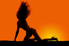 Silhouette woman in bikini on knees and hands hair flipped up Royalty Free Stock Photos