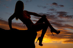 Silhouette woman bikini sit leg crossed. A silhouette of a woman sitting in a bikini in the sunset royalty free stock photography