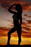 Silhouette of a woman in a bikini standing from side hand on hea Stock Photo
