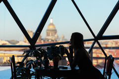 Silhouette of a woman in a cafe with a cup of coffee Stock Photos