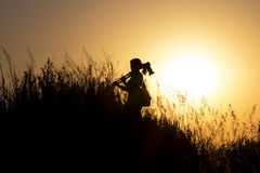 Silhouette of a woman with a camera fixed on a tripod walking up a mountain at sunset Stock Photos