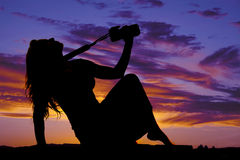 Silhouette of a woman with a camera sitting head back Stock Photo