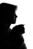 Silhouette of a woman with a cat in her arms Stock Images