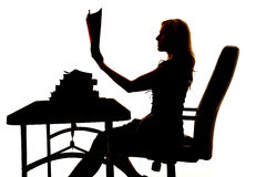 Silhouette of a woman in a chair holding up a book. A silhouette of a woman sitting at a desk, reading a book Royalty Free Stock Photos