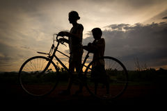 Silhouette of woman and child cycling Stock Photo