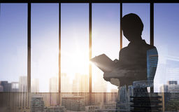 Silhouette of woman with clipboard over city Stock Image