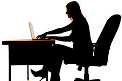 Silhouette woman computer desk type. Silhouette of a woman sitting at a desk typing on a computer Royalty Free Stock Photo