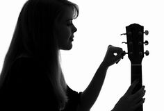 Silhouette of a woman configure a guitar. Black and white silhouette of a young woman configure a stringed musical instrument - a guitar stock photos