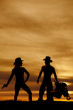 Silhouette of woman cowboy hat with gun down Stock Photos