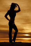 Silhouette woman cowgirl side hand hat. A silhouette of a woman touching her hat looking down Royalty Free Stock Images