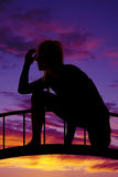 Silhouette of a woman crouched down hand by head Stock Photos