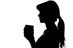 Silhouette of a woman with a cup in hands Royalty Free Stock Image