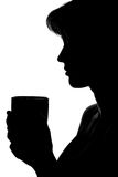 Silhouette of a woman with a cup in hands Stock Photography