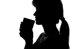Silhouette of a woman with a cup in hands Stock Photos