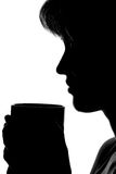 Silhouette of a woman with a cup in hands Royalty Free Stock Photography