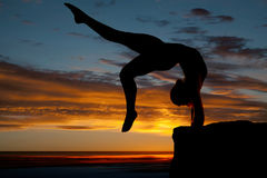 Silhouette of woman dancing back bend legs going back by water Stock Image
