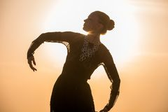 Woman dancing at sunrise. Silhouette of the woman dancing at the beach during beautiful sunrise royalty free stock photography