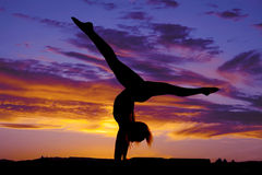 Silhouette of woman dancing on hands legs up out Stock Image