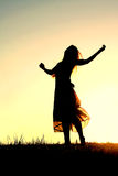 Silhouette of Woman Dancing and Praising God at Sunset. A woman wearing a long skirt, with long blonde hair, is dancing and praising God, while silhouetted Royalty Free Stock Image