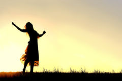Silhouette of Woman Dancing and Praising God at Sunset. A woman wearing a long skirt, with long blonde hair, is dancing and praising God, while silhouetted stock images