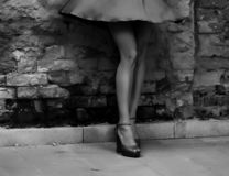 Silhouette of a woman in a dark alley of the city. Women`s feet in heels in a dark alley of the city, Women`s feet in heels in a dark alley of the city royalty free stock image