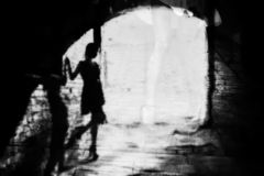 Silhouette of a woman in a dark alley of the city. Women`s feet in heels in a dark alley of the city, Women`s feet in heels in a dark alley of the city stock photo